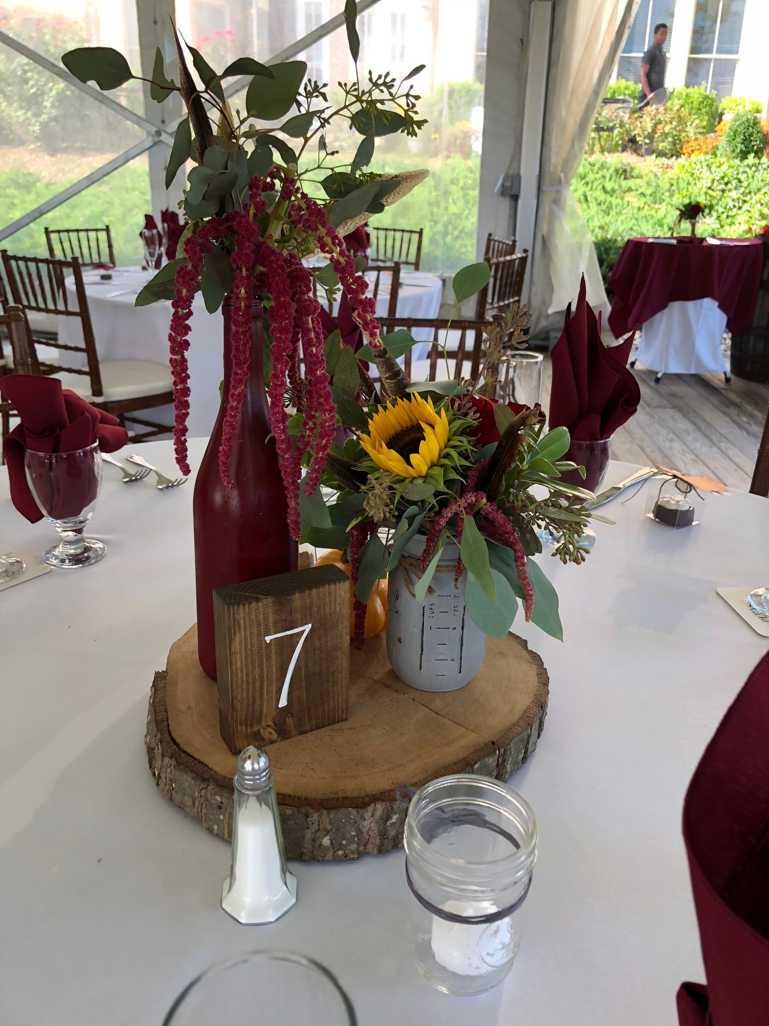 Wood Round With Painted Wine Bottle Arrangements And Table Number